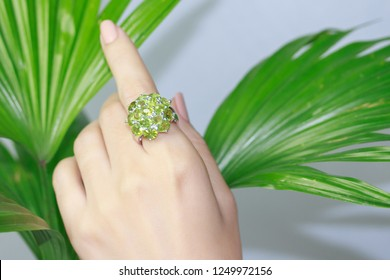 Green peridot Jewel gemstone ring on woman hand put on leaf background