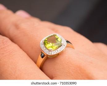 green peridot Jewel gemstone ring on  woman hand put on black background