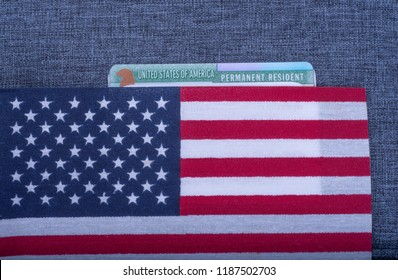 Green Permanent resident card covered American (USA) flag on blue fabric surface.