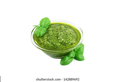 Green pesto sauce and basil, isolated on white