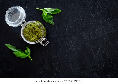 Green pesto sauce in glass jar near basil leaves on black background top view copy space