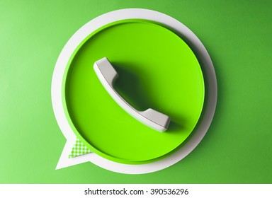 Green phone handset in speech bubble icon made of old phone and tray - flat lay