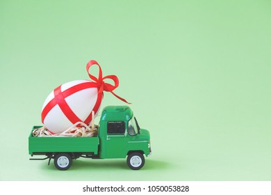 Green pickup toy carrying one decorated easter egg.