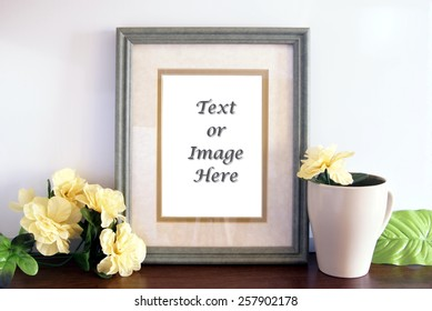Green picture frame sitting on a wood shelf with flowers and a mug sitting next to it. Empty space in the photo frame canvas for adding your text or images.