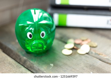 Green piggy Bank with coins and folder on a table
