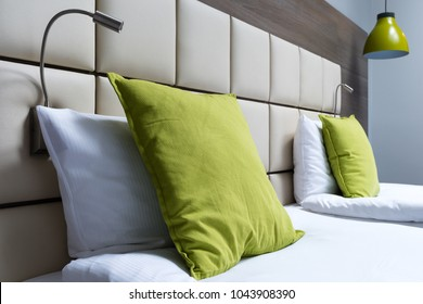 Green pillow, reading lamps and leather bed headboard in modern bedroom