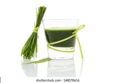Green pills, green powder, green drink and wheat grass blades isolated on white background. Chlorella, spirulina, wheat grass and barley grass. Healthy natural herbal medicine, healthy lifestyle.