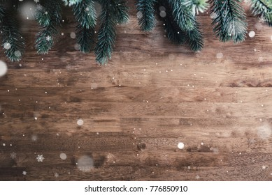 Green pine leaves and snow on wood table,top view  border design Christmas background with copy space