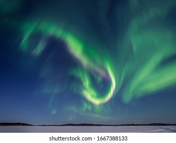 Green and pink Aurora Borealis over Lake Inari in Lapland in Northern Finland.