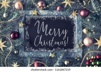 """Green, pink and golden Christmas background with blank black-board. Decorated fir twigs around chalk board on rustic wood with snow. Top view with text """"Merry Chtistmas!"""""""