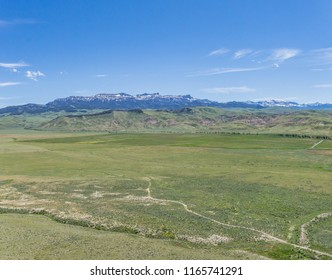 Green plains and farmlands below the high ridges of the Rocky Mountains.
