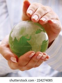 Green planet in women's hands.