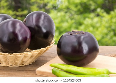 Green plant background, eggplant placed on wooden table