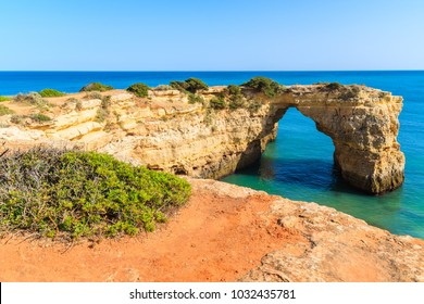 Green plants on cliff and view of rock arch on sea near Armacao de Pera town , Algarve, Portugal