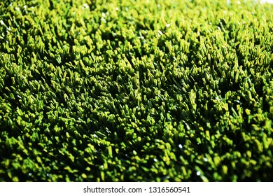 Green plastic astroturf fake grass close up