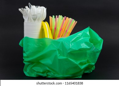Green plastic bag with single use straws plates cups and cutlery waste garbage as recycle pollution junk ecology concept on black background
