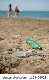 Green, plastic bottle, cotton swabs, cap, box and cigarettes left on a sandy beach with walking people in background.