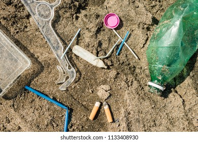 Green, plastic bottle, cotton swabs, cap, box and cigarettes left on a sandy beach.