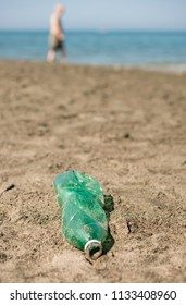 Green, plastic bottle left on a sandy beach with walking people.