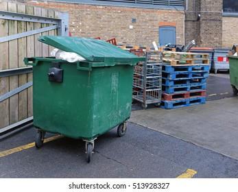 Green Plastic Garbage Bin Behind Warehouse