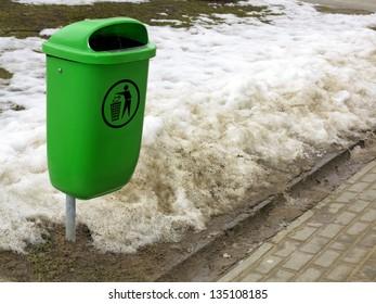 Green plastic garbage bin or can on street winter scenery