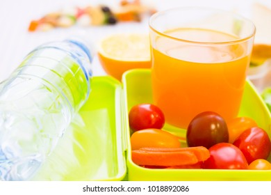 A green plastic lunch box with cherry tomatoes, carrot, a glass of juice and a bottle of water, close up, white squared paper background with copy space