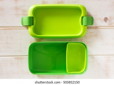 Green plastic lunch box on wooden background