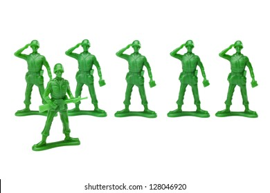 Green plastic military toys doing a salute to there captain over a white background