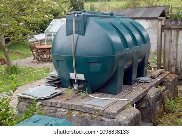 Green plastic oil tank in a rural garden of a cottage in Cornwall.