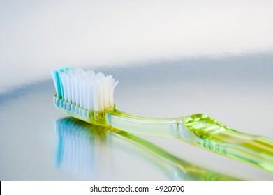 Green plastic toothbrush reflected on metallic surface.