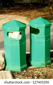 Green plastic trash recycling container in the park