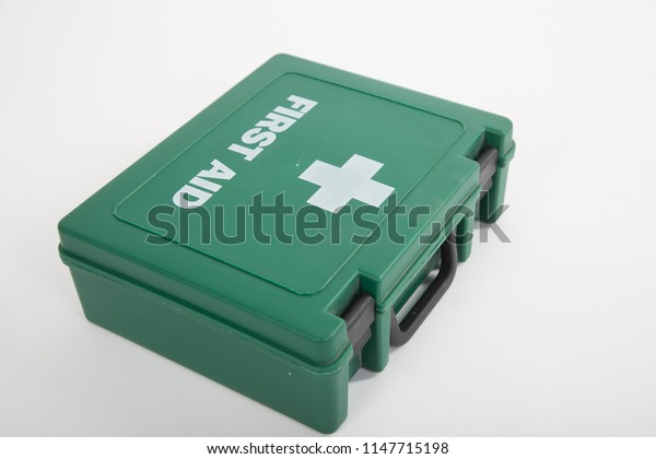 Green plastic UK first aid box with white cross and first aid text. close up and isolated on white background, studio.