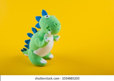 Green plasticine figure of Tyrannosaurus Rex on yellow background