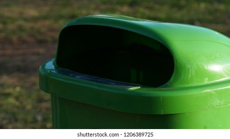 A green plasticl trash bin in the park or outside of a public utility building