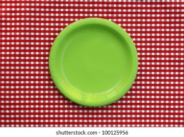 Green plate isolated on red and white checked tablecloth
