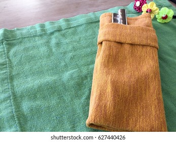 Green plate napkin and brown napkin have a fork and knife inside with three colorful flowers.