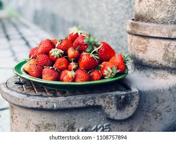 A green plate with strawberries