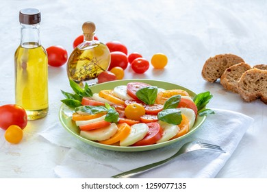 Green plate with traditional Italian Caprese salad and olive oil bottles, tomatoes and bread on white table.