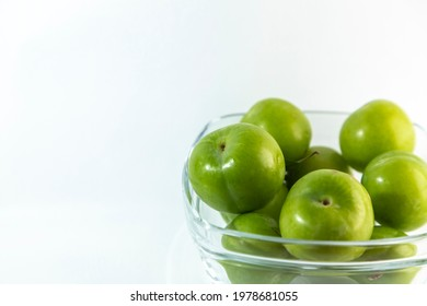 green plums in glass bowl