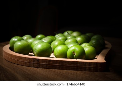 Green plums in a wooden plate.