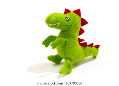Green plush dinosaur doll, isolated on white.