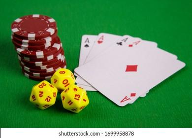 table de jeu de poker vert avec des jetons rouges, des cartes de jeu et des dés jaunes