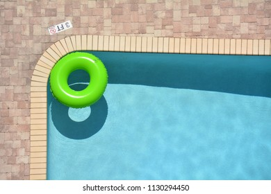green pool float in a refreshing cool blue swimming pool.