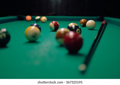 Green pool table with balls and cue.