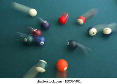 Green pool table with balls in motion