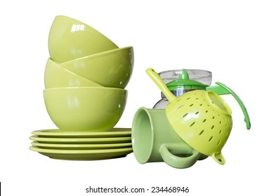 green porcelain dishes with bowls, plates, mug, teapot and tea-strainer isolated on white