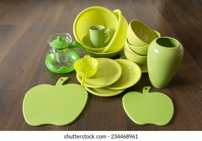 green porcelain dishes on a dark wood floor