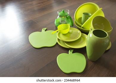 green porcelain dishes on a dark wooden parquet