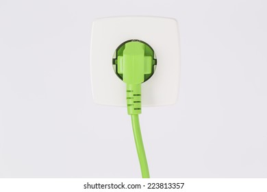 Green power plug into power outlet against a white background