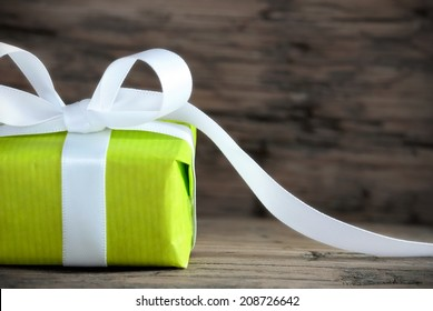 Green Present on Wood with White Ribbon and Copy Space